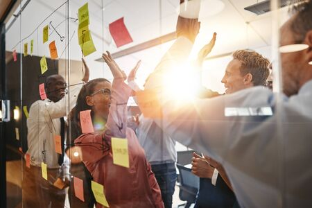 Group of diverse businesspeople celebrating together with high fives after a brainstorming session with sticky notes on a glass wall in a modern office