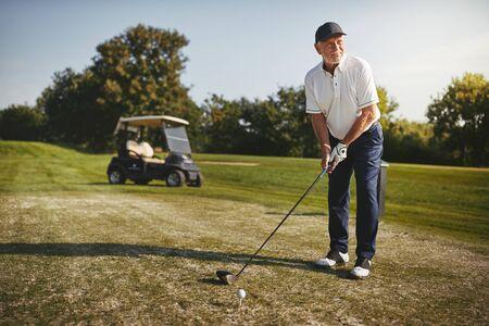 Sportlicher Senior, der an einem sonnigen Tag mit seinem Fahrer eine Runde Golf spielt Standard-Bild