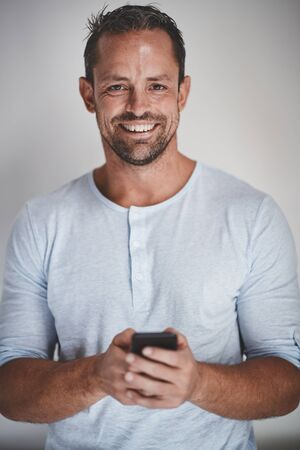 Casually dressed male entrepreneur reading a text message on his cellphone and smiling while standing against a gray background