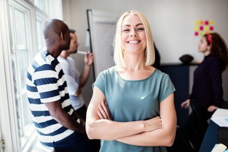 Confident young female designer standing with her arms crossed after a meeting in an office with colleagues working together in the background