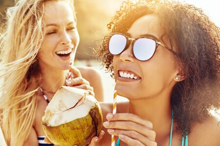 Two young female friends in bikinis laughing while sipping from coconuts on a sandy tropical beach during summer vacation