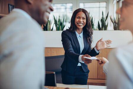 Jeune concierge afro-américain sympathique debout derrière un comptoir de réception donnant des informations sur la chambre à deux invités s'enregistrant dans un hôtel