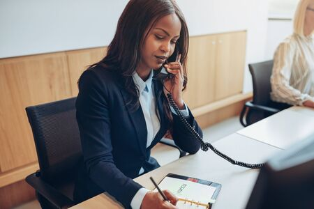 African American businesswoman writing down notes and talking on a telephone while working with a colleague at a desk in an office reception area Фото со стока