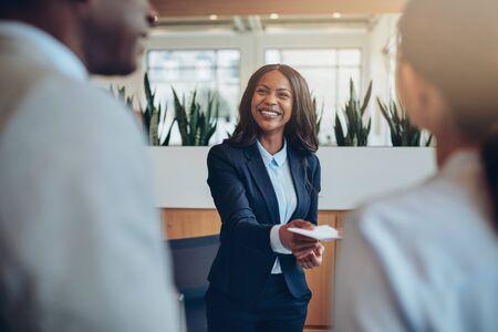 Concierge afro-américain souriant debout derrière un comptoir de réception donnant des informations sur la chambre à deux invités s'enregistrant dans un hôtel Banque d'images
