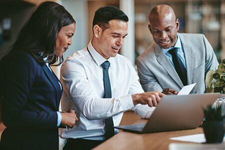Diverse Gruppe lächelnder Geschäftsleute, die zusammen Papierkram lesen, während sie an einem Laptop an einem Tisch in einem Büro arbeiten Standard-Bild
