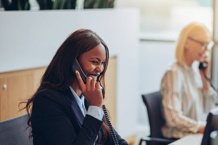 African American businesswoman talking on a telephone and laughing while working at an office reception with a colleague