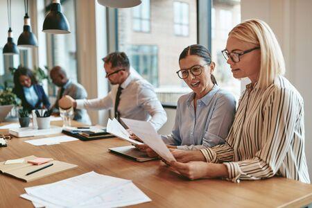 Dos sonrientes jóvenes empresarias leyendo el papeleo juntos mientras están sentados en una mesa de juntas durante una reunión de oficina