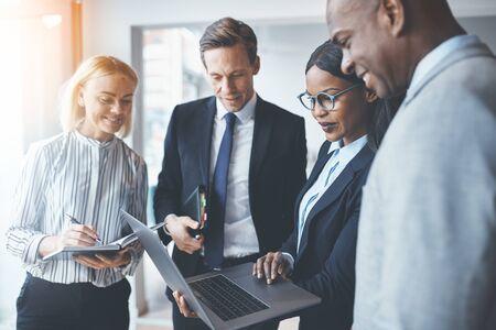 Grupo diverso de empresarios sonrientes de pie en una oficina moderna y luminosa discutiendo trabajar juntos y usando una computadora portátil