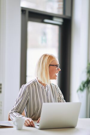 Laughing young businesswoman working on a laptop and talking with an unseen colleague in an office Stock Photo