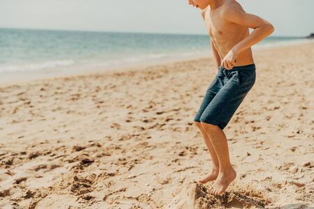 Cute little boy jumping in the sand on a tropical beach on a sunny day during summer vacation