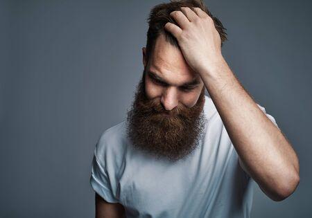 Hombre joven con estilo con una larga barba vistiendo una camiseta de pie con la mano en el pelo contra un fondo gris