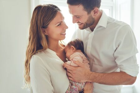 Loving young couple standing together in their living room at home cradling the adorable baby girl