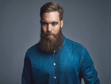 Hip and stylish young man with a long beard looking deep in thought while standing alone against a gray background Imagens