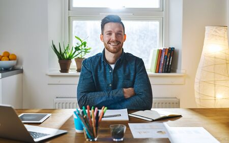 Confident smiling bearded man with folded arms in casual clothes sitting at desk in front of bright window 免版税图像