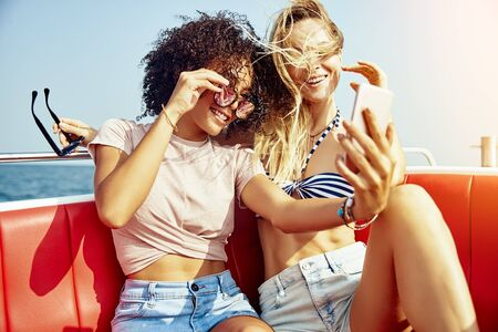Two smiling young women sitting on a boat on the ocean taking selfies together during their summer vacation