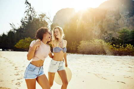 Two young female friends laughing while walking together along a sandy beach on a sunny day during their summer vacation