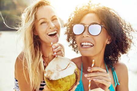Two laughing young friends wearing bikinis and drinking from coconuts while standing together on a sandy beach during summer vacation