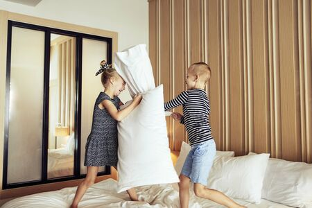 Cute little brother and sister laughing while having a pillow fight together on their bed at home