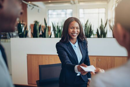Smiling African American concierge working behind a hotel counter giving two guests their hotel information during check in