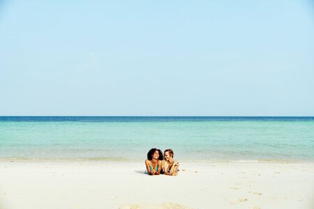 Two smiling young female friends in bikinis suntanning together on a sandy beach during a tropical vacation