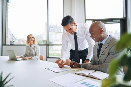 Two smiling businessmen discussing paperwork with a coworker in a background during a meeting around a boardroom table Banque d'images