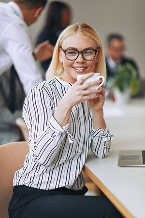 Smiling young businesswoman sitting at a boardroom table drinking a cup of coffee with coworkers talking in the background
