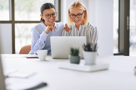 Two laughing young businesswomen sitting together at a table in an office boardroom working on a laptop Banque d'images