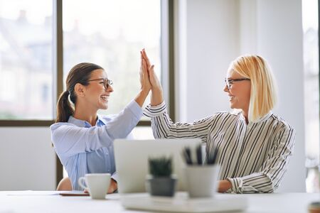 Two smiling young businesswomen high fiving together while sitting at an office table working on a laptop