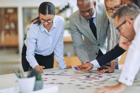 Diverse group of smiling businesspeople standing together around an office table trying to solve a jigsaw puzzle