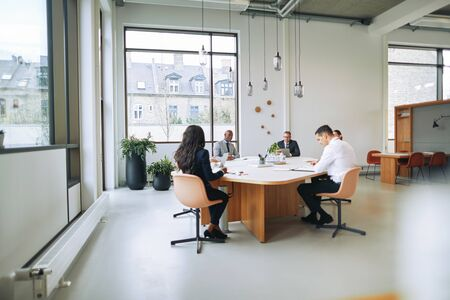 Group of diverse businesspeople talking together while sitting around a boardroom table in an office