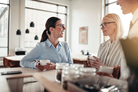 Smiling young businesswoman talking with two colleagues during their coffee break together in a bright modern office