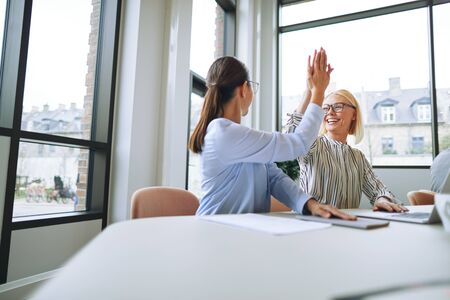 Two smiling young businesswomen celebrating with high fives while working at a boardroom table with colleagues in the background 版權商用圖片