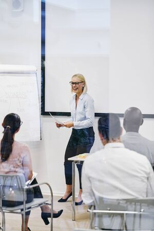 Young manager laughing while explaining business concepts to a group of staff sitting inside of an office meeting room Banque d'images