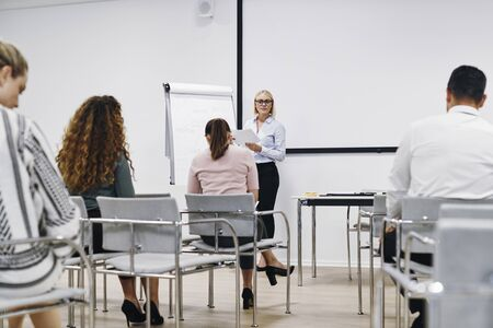 Young manager talking with a group of employees while giving a presentation in the meeting room of an office