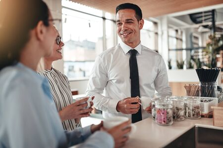 Group of smiling young businesspeople chatting together during their coffee break in a bright modern office