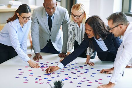 Diverse group of smiling businesspeople working together around a boardroom table in an office trying to solve a jigsaw puzzle Banque d'images