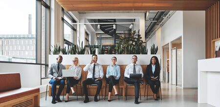 Smiling group of diverse businesspeople sitting in chairs together in an office reception waiting for their meeting