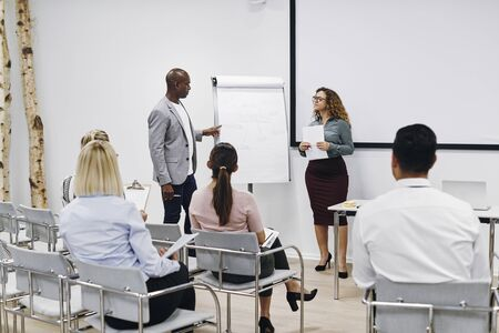 Two diverse work colleagues discussing business concepts during a flip chart presentation in an office seminar room