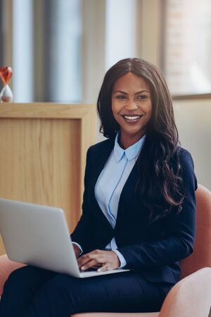 Smiling young African American businesswoman sitting in a chair in the lounge of a modern office working on her laptop