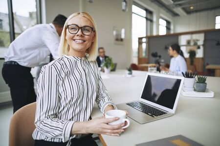 Smiling young businesswoman sitting at a boardroom table and drinking coffee with colleagues working in the background Banque d'images