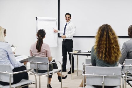 Businessman laughing while giving a flip chart presentation to a group of staff in the seminar room of an office
