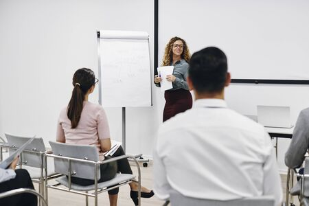 Young businesswoman giving a flip chart presentation to a group of a colleagues in the seminar room of an office