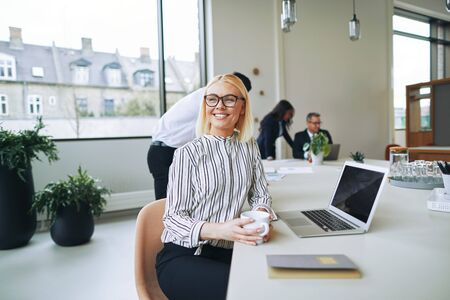 Smiling young businesswoman enjoying a coffee and thinking about her workday while sitting at a boardroom table with colleagues in the background Banque d'images
