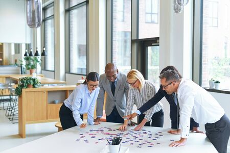 Smiling group of diverse businesspeople standing together around a boardroom table in an office trying to solve a jigsaw puzzle