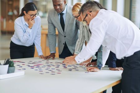 Diverse group of businesspeople standing together around a boardroom table in an office focused on trying to solve a jigsaw puzzle