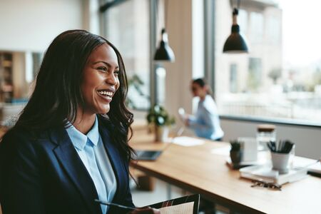Young African American businesswoman laughing while walking in an office after a meeting with colleagues Banque d'images
