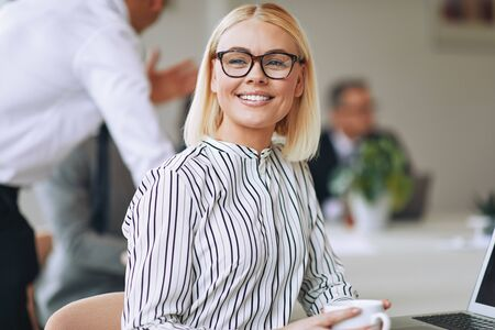 Smiling young businesswoman sitting at a boardroom table drinking a coffee with colleagues working in the background
