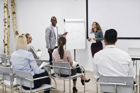 Two diverse colleagues laughing while giving a flip chart presentation to staff in an office seminar room Banque d'images