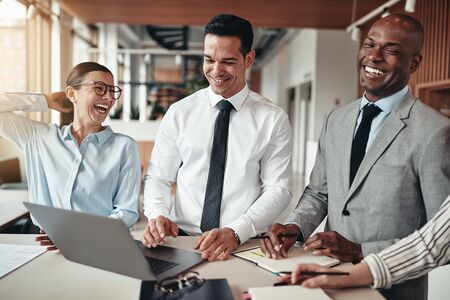 Laughing group of diverse businesspeople working together on a laptop and going over paperwork while standing at a table in a modern office Banque d'images