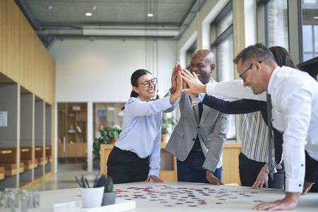 Diverse group of smiling businesspeople high fiving together around a boardroom table in an office while trying to solve a jigsaw puzzle Banque d'images